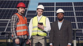Trio of solar panel engineers outside. Trio of solar panel multi ethnic engineers and executive surrounded by large collector arrays outside looking camera stock footage