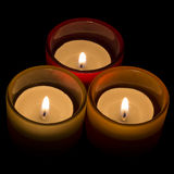 Trio of tea-lights arranged in a triangle. Three candles burning over a black background Stock Photography