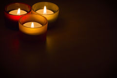 Trio of tea-lights with text space. Three candles burning over a black background with text space Royalty Free Stock Images