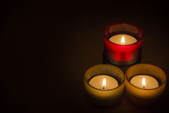 Trio of tea-lights with text space. Three candles burning over a black background with text space Stock Photo