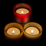 Trio of tea-lights. Three candles burning over a black background Royalty Free Stock Images
