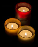 Trio of tea-lights. Three candles burning over a black background Stock Images