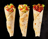 Trio of Tex Mex Fajita Wraps on Black Background. High Angle Still Life of Trio of Tex Mex Fajita Wraps on Black Background - Variety of Grilled Flour Tortilla royalty free stock images