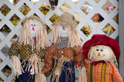 Trio of scarecrows. A trio (three) of scarecrows smile as they wait outside a home, ready to greet visitors Stock Photo