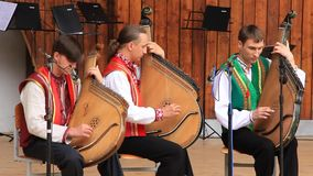 Trio. UKRAINE, KIEV, MAY 29, 2010: Three men in national costume playing bandura (Ukrainian stringed instrument) at ceremonial parade and performance dedicated stock footage