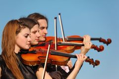 Trio of violinists plays against sky Royalty Free Stock Photo