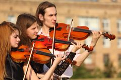 Trio of violinists plays outdoor. Day Royalty Free Stock Photo