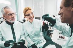 Trio von den lächelnden medizinischen Arbeitskräften, die Aufgabe abschließend genießen stockbild