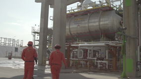 Trio of workers move from zone. Refinery installations plant in operation stock footage
