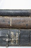Trio of Worn Antique Leather Bibles with Antique Cross in Wood a. Close up trio of antique leather bibles stacked with one antique cross made of wood metal and royalty free stock photography