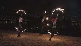 Fireshow performers dancing with fire on sand stock footage