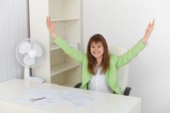 Triomfantelijk meisje op kantoor op werkplaats Stock Fotografie