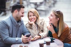 Triovrienden die telefoon in openluchtkoffie met behulp van Royalty-vrije Stock Afbeelding
