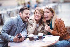 Triovrienden die telefoon in openluchtkoffie met behulp van Royalty-vrije Stock Afbeeldingen