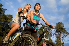 During trip. Photo of cyclists on their bikes in park or forest during summer vacations Stock Photos
