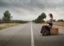 Trip. Woman sitting on a suitcase on a countryside road and reading a book Royalty Free Stock Images