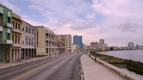 A trip along the Malecon seafront in the Cuban city of Havana. Driving along the promenade along the ocean, past old houses and buildings in the ancient Cuban stock video footage
