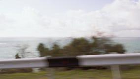 A trip along the mountains along the sea coast. Traveling by car along the mountains along the sea coast traffic along the road fence stock video footage