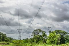 View with typical tropical landscape and electric tower and power lines, baobab and other trees and other types of vegetation,. Trip through Angola's lands stock photos