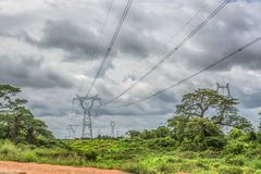 View with typical tropical landscape and electric tower and power lines, baobab and other trees and other types of vegetation,. Trip through Angola's lands royalty free stock image