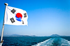 Trip boat on Jeju island, South Korea. South Korean flag hang on fast boat ferry leaving Jeju island in South Korea royalty free stock images