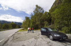 Trip break. Three tourists taking a break while travelling in Norway, a car (Volvo) at the side of the road Royalty Free Stock Photo
