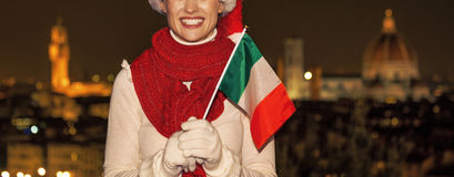 Smiling woman in Christmas hat in Florence with Italian flag Royalty Free Stock Images