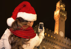 Woman in Christmas hat in Florence with cellphone taking photo Royalty Free Stock Photo