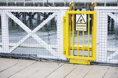 Trip hazard caution sign on ferry ship yellow gate. Uk stock photo