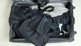 Trip, luggage and people concept - man packing clothes into travel bag. Business, trip, luggage and people concept - man packing clothes into travel bag stock footage