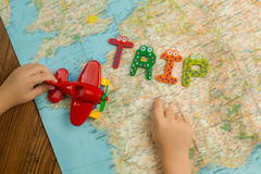 Trip theme. Trip mood theme. Kid`s hands with red toy plane above the map. Top view Royalty Free Stock Photo