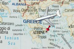 Trip to Athens with toy airplane and push pin. On map of Greece Stock Image