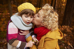 Trip to forest during the autumn. Mother giving a kiss girl on cheek Stock Photography