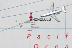 Trip to Hawaii with toy airplane and push pin. On map Stock Photos