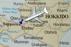 Trip to Hokkaido with toy airplane and push pin. On map of Japan Royalty Free Stock Images