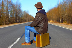 Trip to holiday. Travel to a week-end.The man in jeans with a suitcase. The man sits on a suitcase on the asphalted empty road Royalty Free Stock Images