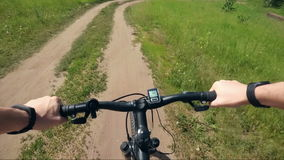 Trip to mountain bike from the first-person hand the wheel and road dust stock footage