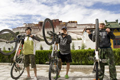Trip to Tibet by bike  successfully. Three young men lifting their bikes in front of  the Potala Palace in Lhasa  to celebrate their success of the long journey Stock Images