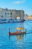 The trip on traditional dghajsa water taxi, Birgu, Malta. BIRGU, MALTA - JUNE 17, 2018: The colorful wooden dghajsa water taxi with tourists on the trip to three Royalty Free Stock Photo