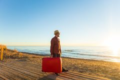 Trip, travel, summer and holidays concept - a man with red case is standing on a beach and watching a sunset.  royalty free stock images