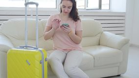 Trip, travel, and vacations concept - woman with yellow suitcase is waiting for the taxi. Or carsharing stock video