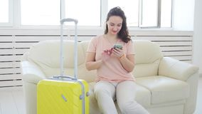 Trip, travel, and vacations concept - woman with yellow suitcase is waiting for the taxi. Or carsharing stock footage