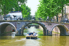 The trip under the bridges. The scenic canal Leidsegracht boasts a lot of bridges, Amsterdam, the Netherlands Stock Photo