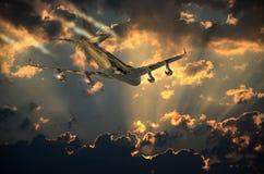 Trip under the sunset. Big plane flying toward the sunrise Royalty Free Stock Photo