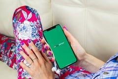 Tripadvisor在苹果计算机iPhone x屏幕特写镜头的应用象在妇女手上 tripadvisor com app象 黑板企业白垩黑板画媒体网络网络连接人照片社交的概念连接数 soc. 库存图片