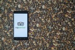 Tripadvisor-Logo auf Smartphone auf Hintergrund von kleinen Steinen Lizenzfreie Stockfotos
