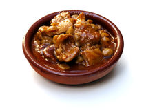 Tripe with chickpeas. Served in a clay plate surrounded by white background royalty free stock photography