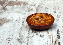 Tripe with chickpeas. Served in a clay pot surrounded by rustic background stock photography