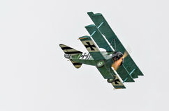Triplane fighter flying on sky Royalty Free Stock Photo
