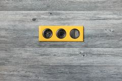 Triple Bright Yellow Frame With Power Socket, Usb Ports And Light Key Switch On Grey Wooden Wall Royalty Free Stock Photography